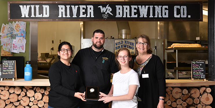 Deaf and Hard of Hearing Academic Bowl participants smiling and posing with award at Wild River Pizza