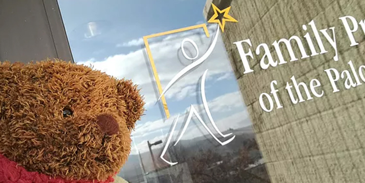 Teddy bear in front of Family Promise of Palouse logo