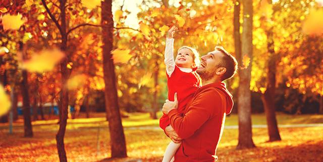 Father and child on a walk through park in autumn