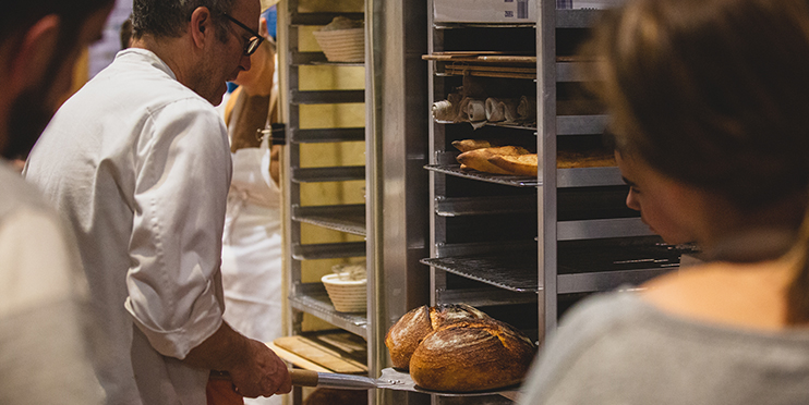 Man putting homemade bread away to cool