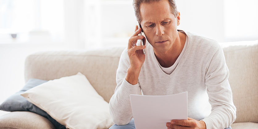 Concerned man talking on phone looking at paper
