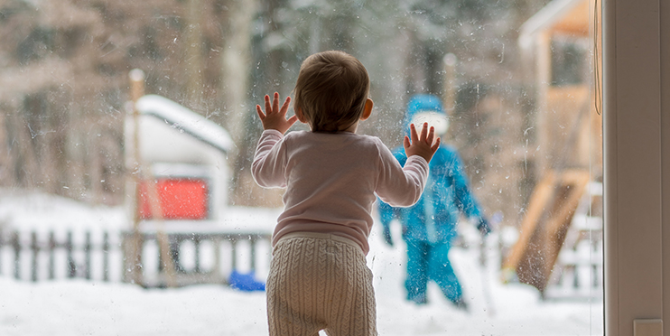 Child looking outside on a snowy day with older sibling playing outside