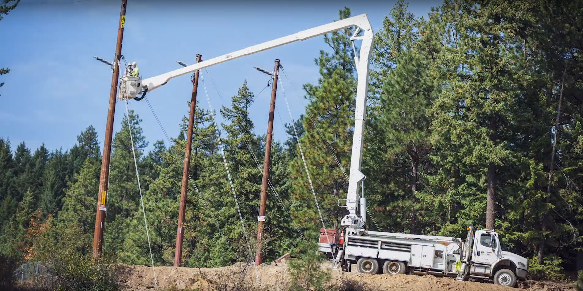 Bucket truck and employees working on electric power line