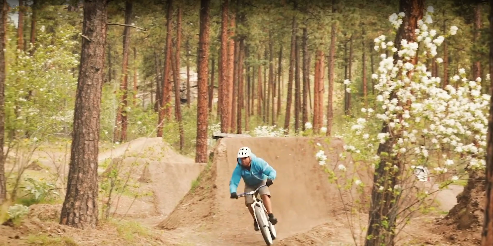Man biking outside on a dirt track with jumps