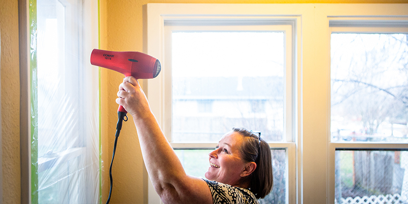 Woman using hairdryer to apply plastic to windows for energy efficiency
