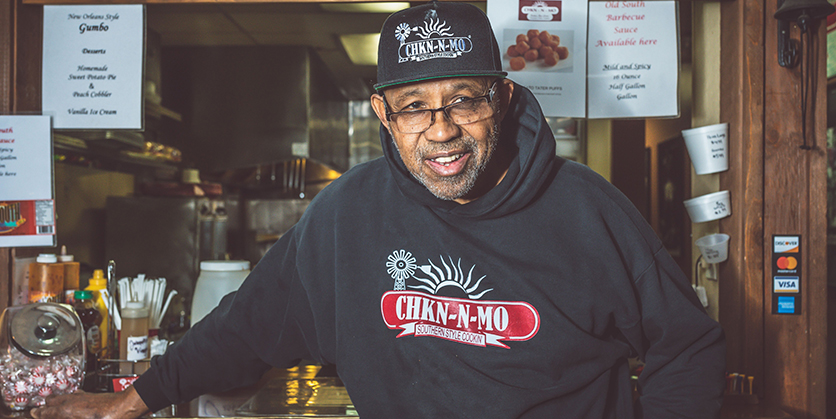Owner of Chkn-N-Mo standing in his restaurant, smiling