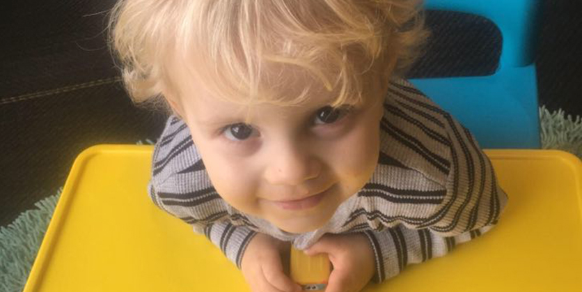 Little boy leaning forward on yellow table, smiling