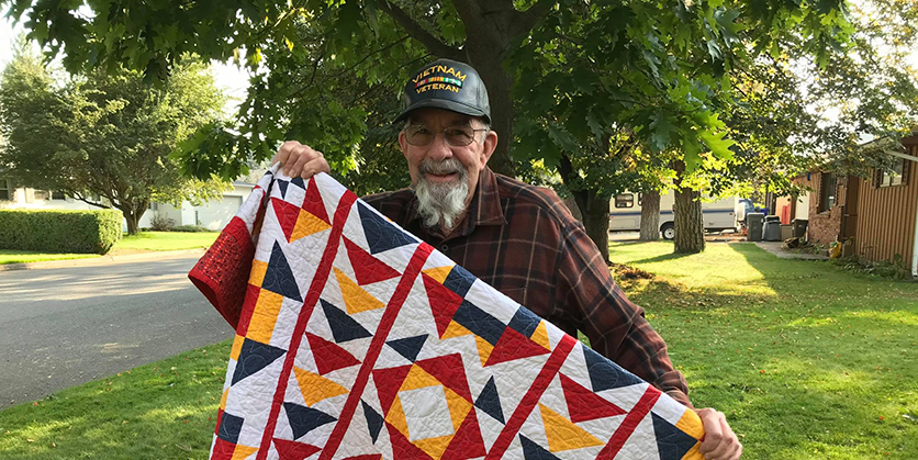 Man wearing a veteran's hat, holding up a quilt and smiling