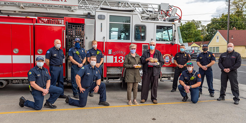 Firefighters posing with man and woman who are holding cookies