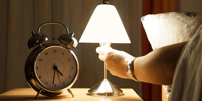 Hand turning on a lamp. A clock sits next to the lamp on a bedside table.