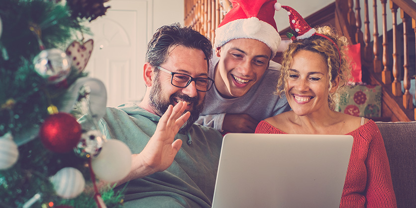 Three people are on a video call for the holidays - one man is wearing a Santa hat and the woman is wearing a headband with a smaller Santa hat. The man in glasses is waving