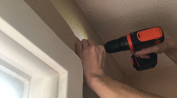 Closeup of a person's hands - using a drill to install a curtain rod