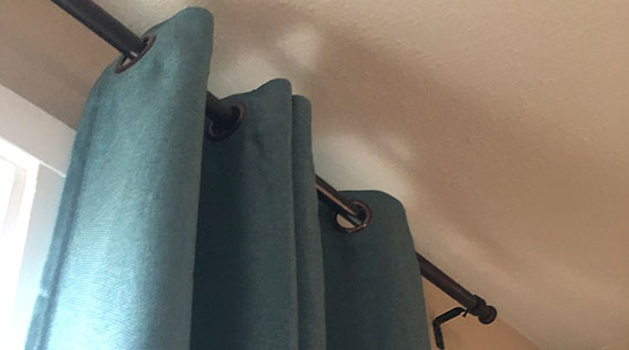 Closeup of curtain rod and drapes