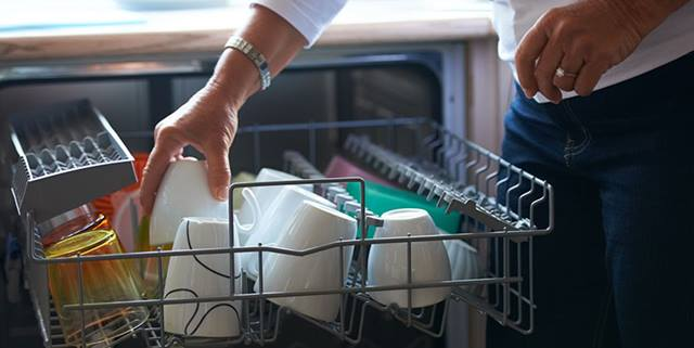A woman loads her dishes into the dishwasher