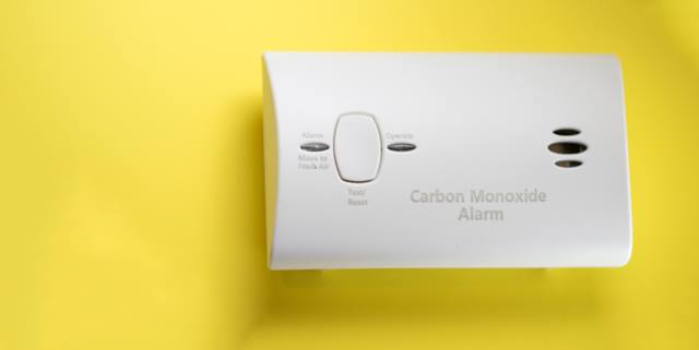 Carbon monoxide detector on yellow background