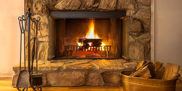 Stone fireplace with logs burning in a residential home