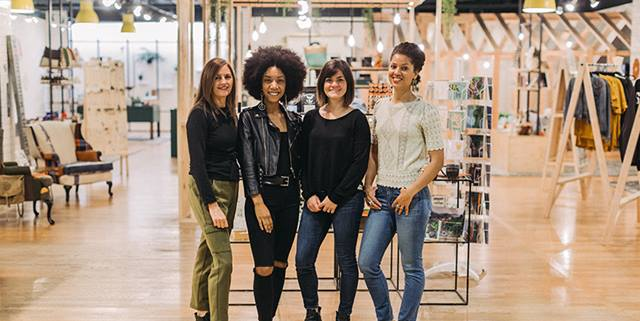 In the retail shop, From Here, four women stand and smile
