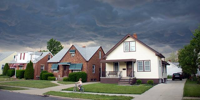 Boy rides bike on sidewalk in front of houses, rushing home as there are storm clouds in the sky
