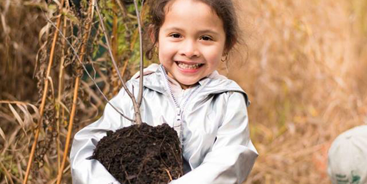 Little girl smiling holding a small tree