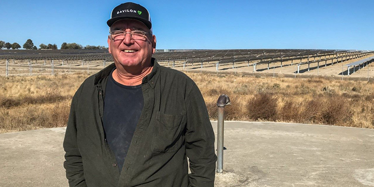 Man smiling in front of solar farm