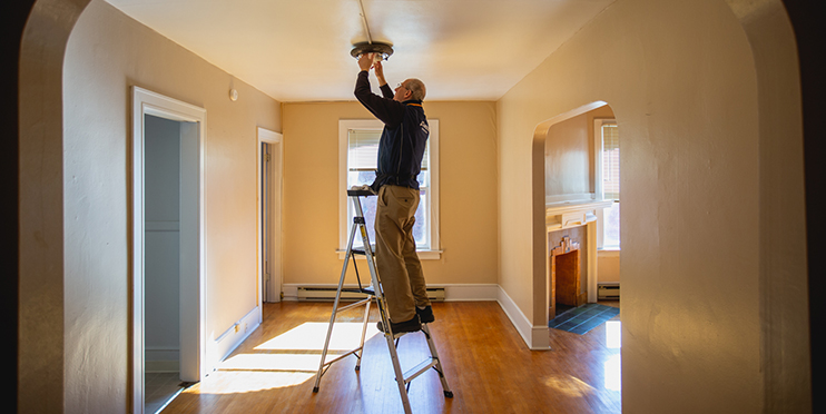 Person changing light bulb on ladder
