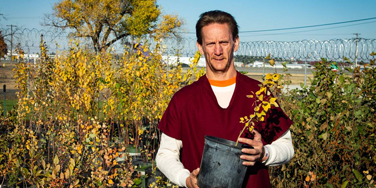 Male inmate smiling holding small potted tree
