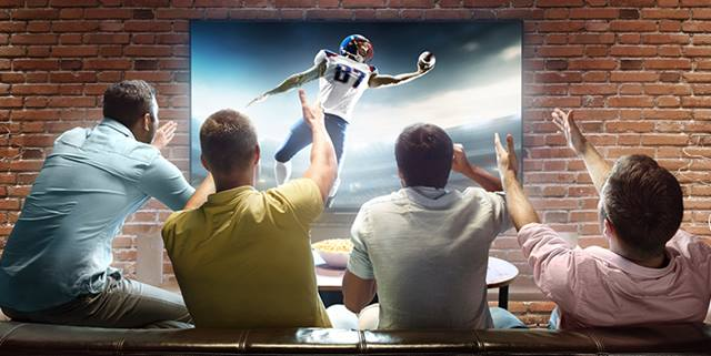 Four men sitting on a couch watching football on the tv and cheering