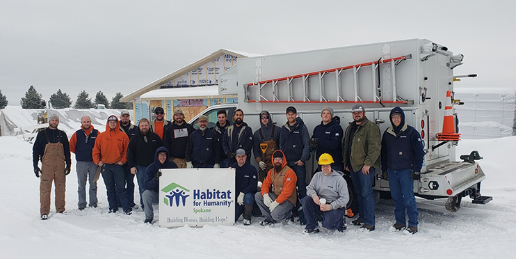 Avista employees posing with Habitat for Humanity sign in front of house