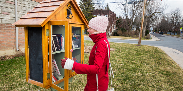 Woman looking at book from a sidewalk library