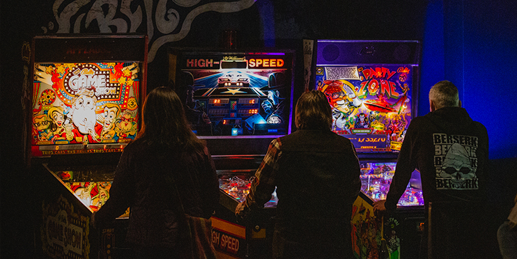 Three people playing pinball machines