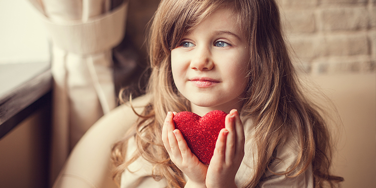 Girl holding sparkly heart in hands