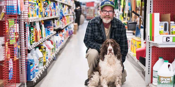 Man smiling with dog in hardware store