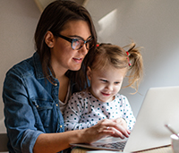 Mother with young daughter on laptop