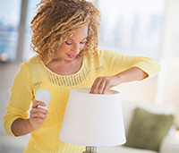 Woman changing lightbulb in a lamp