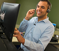 Man looking at computer talking on headset
