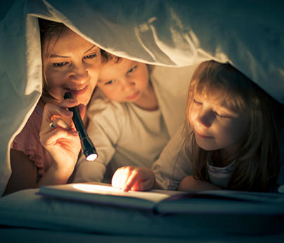 Mother, little girl, and little boy under a blanket reading a book by flashlight