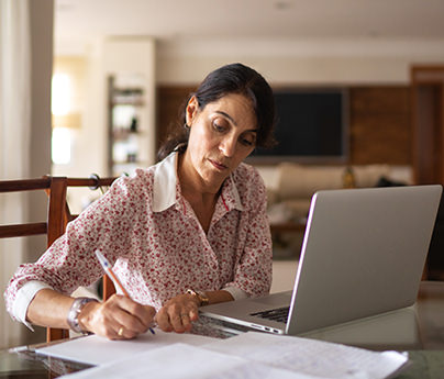 Woman filling out paperwork in front of laptop
