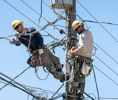 Two linemen working on a power pole with a blue sky