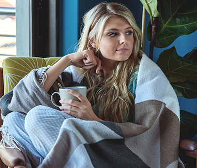 Woman with blanket and mug