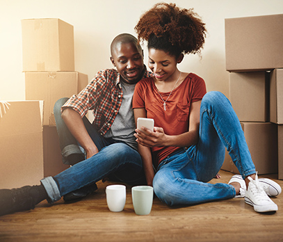Man and woman sitting among moving boxes looking at phone